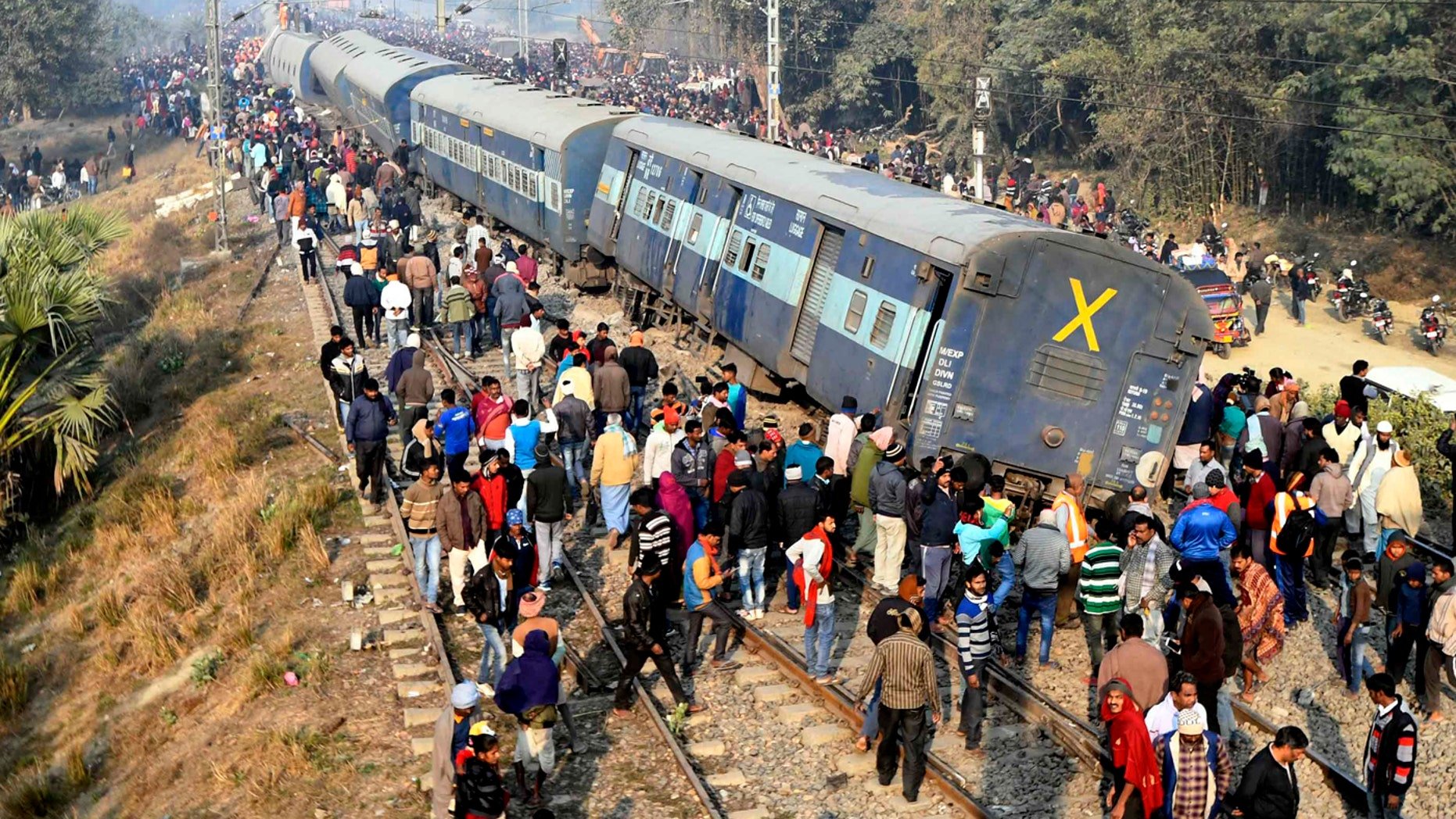 Rescue workers look for survivors as locals stand around the derailed coaches of a train, 20 miles north of Patna, the Bihar state capital of India, Sunday, Feb. 3, 2019.