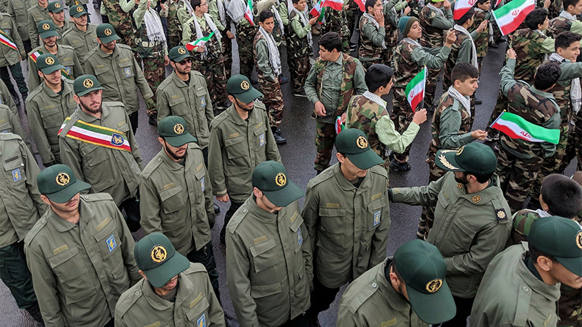 School students wave their national flags as Revolutionary Guard members arrive in Azadi, freedom square, during a ceremony celebrating the 40th anniversary of Islamic Revolution, in Tehran, Iran, on Monday.