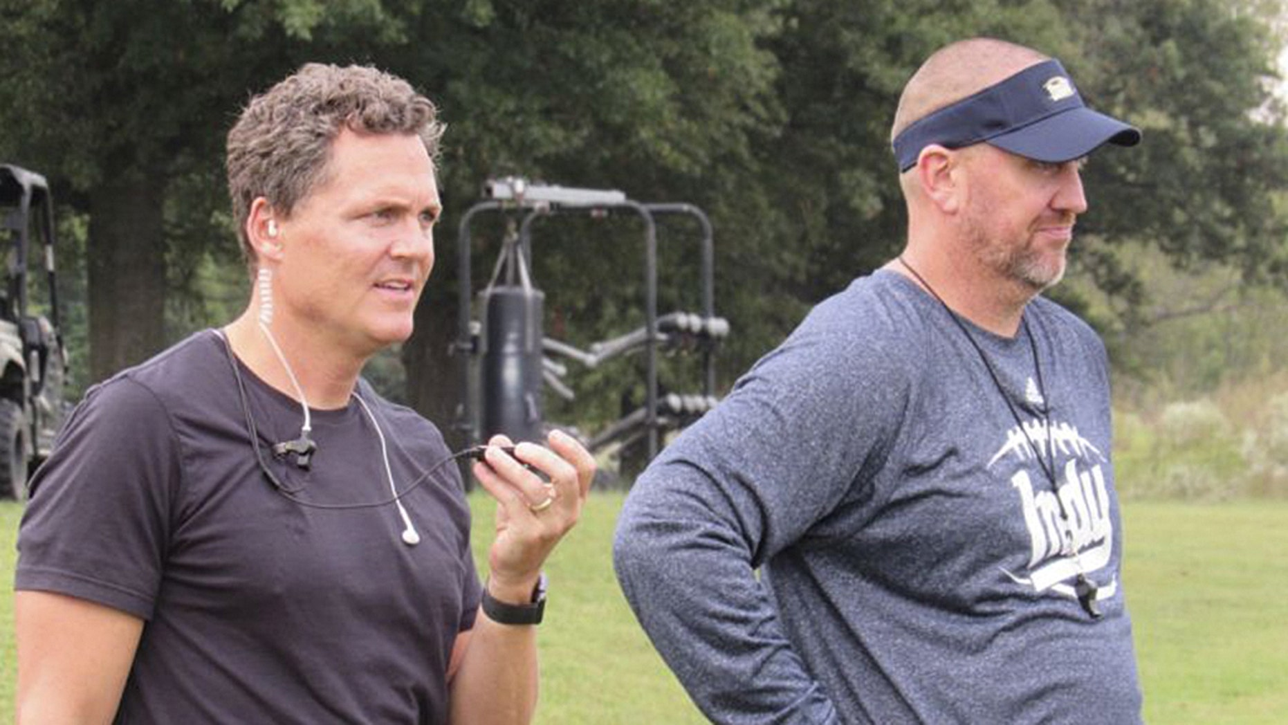 """Director Greg Whiteley, left, and Independence Community College football coach Jason Brown, watch a practice during a shoot for the Netflix series """"Last Chance U."""" in Independence, Kan. The series exposes the grim and gritty world of high-stakes junior-college football."""
