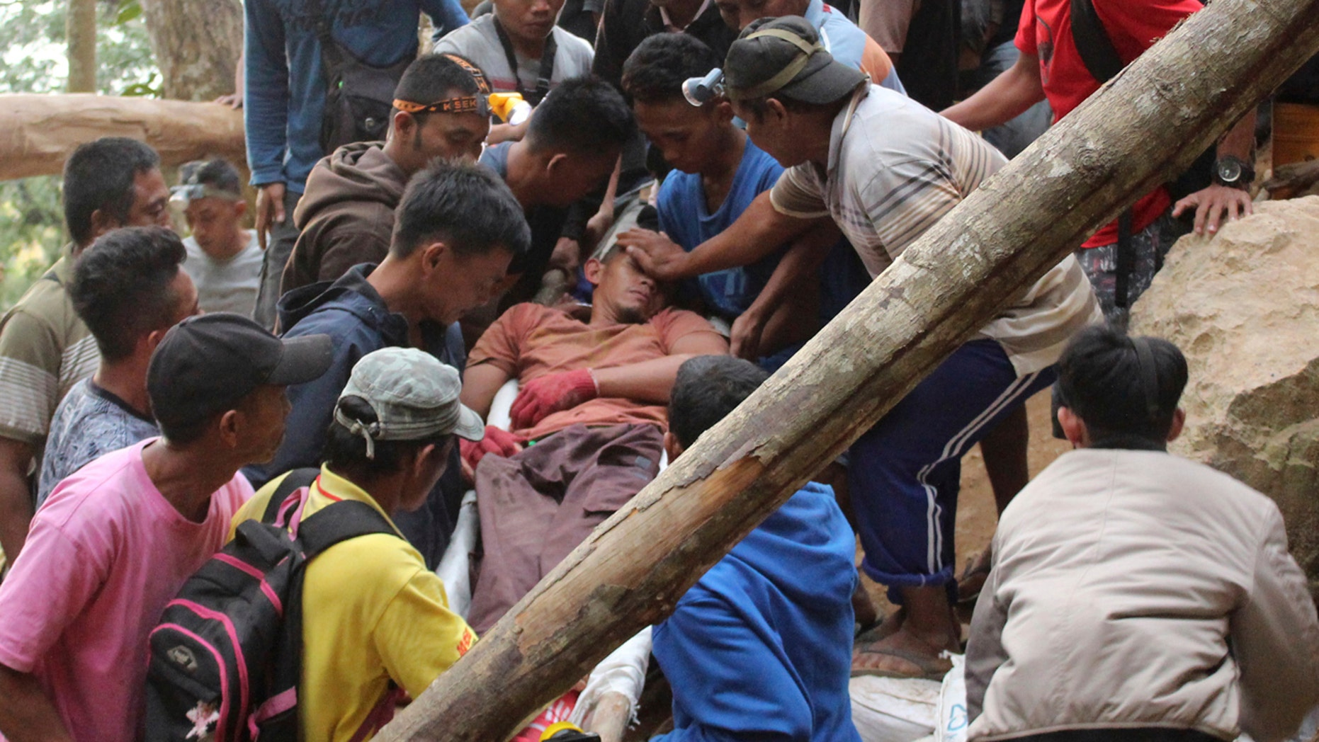 Rescuers carry a survivor from inside a collapsed mine in Bolaang Mongondow, North Sulawesi, Indonesia, Wednesday, Feb. 27, 2019.