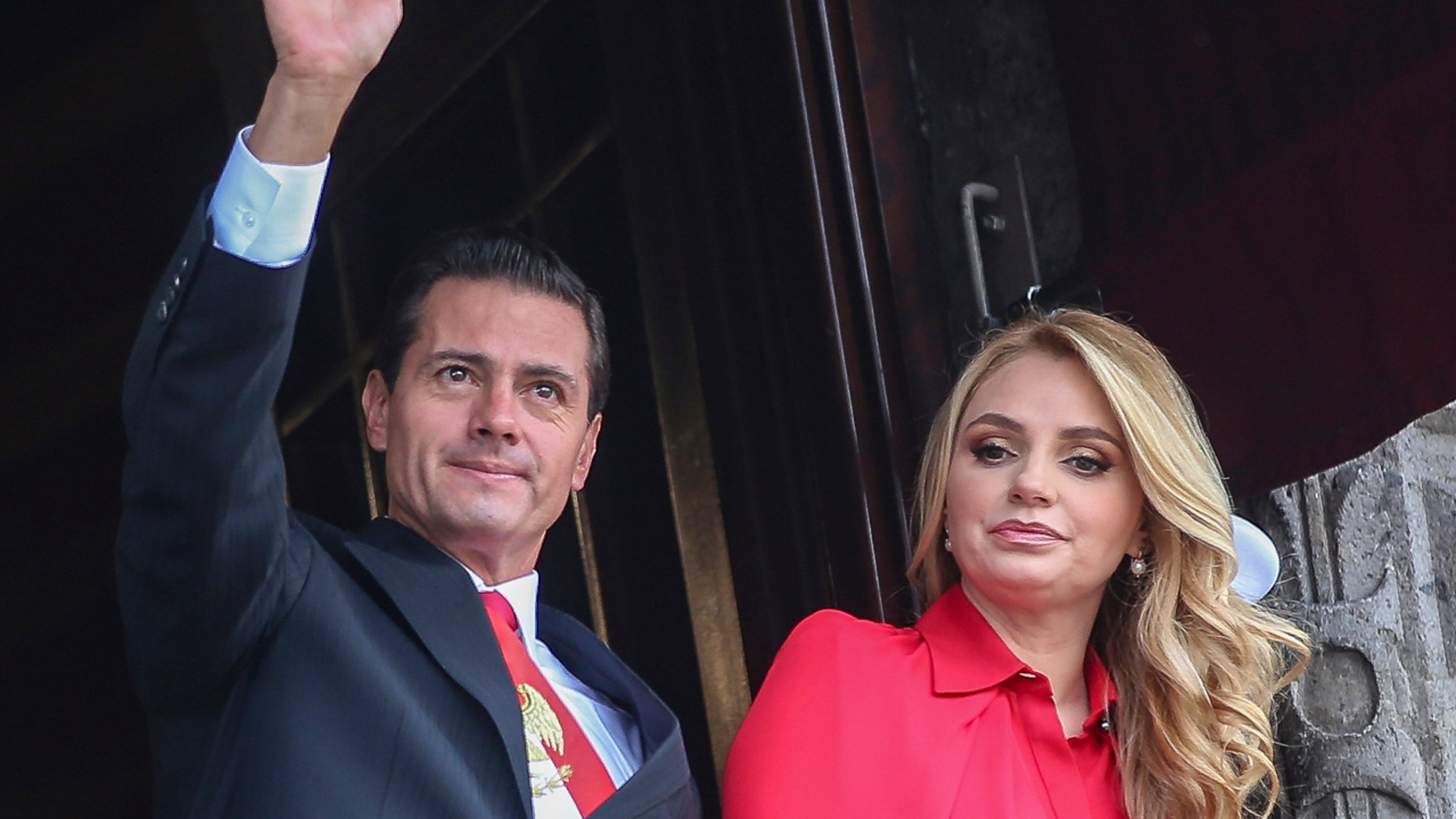 In this Sept. 16, 2018 file photo, Mexico's President Enrique Pena Nieto waves from a National Palace balcony, accompanied by first lady Angelica Rivera, during the Independence Day military parade in the Zocalo of Mexico City. (AP Photo/Anthony Vazquez, File)