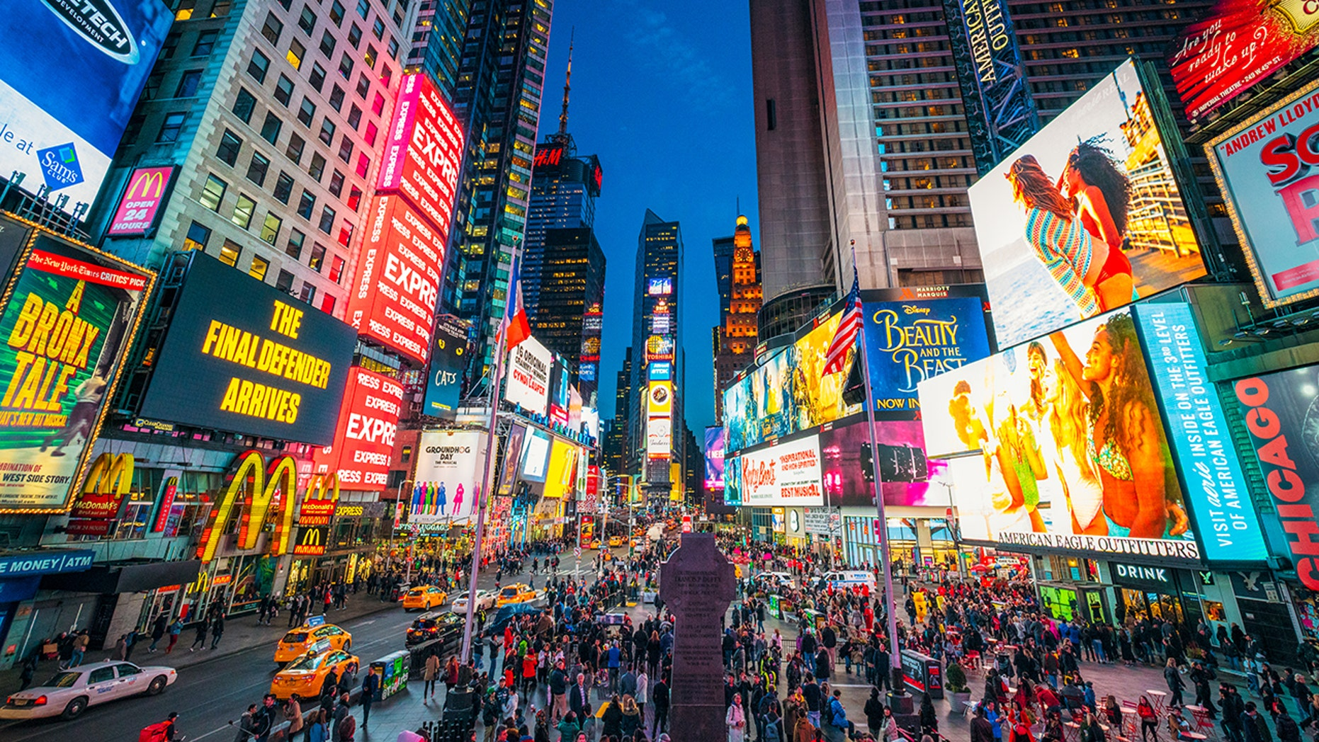 Times Square covered with illuminated billboards during the 'blue hour' period at dusk, with tourists on the streets.