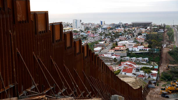 In this Jan 15, 2019 image, a section of newly-replaced border wall separates Tijuana, Mexico, above left, from San Diego, right, in San Diego. Border Patrol officials say some Mexican homes and structures encroach on U.S. soil posing a dilemma for authorities when replacing the wall. (AP Photo/Gregory Bull)