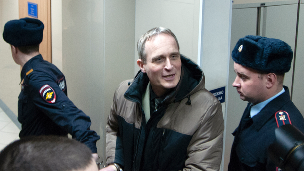 Danish Jehovah's Witness Dennis Christensen is escorted from a courtroom in Russia in February. (Yuriy Temirbulatov, Courtesy of Jehovah's Witnesses via AP)