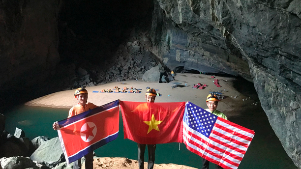 In this Monday, Feb. 15, 2019, drone image, cave explores pose with flags of North Korea, Vietnam and the U.S. in En cave in Quang Binh province, Vietnam. Vietnam will host the second summit between U.S. President Donald Trump and North Korean leader Kim Jong Un in Hanoi on Feb. 27-28. (Oxalis Adventure via AP)