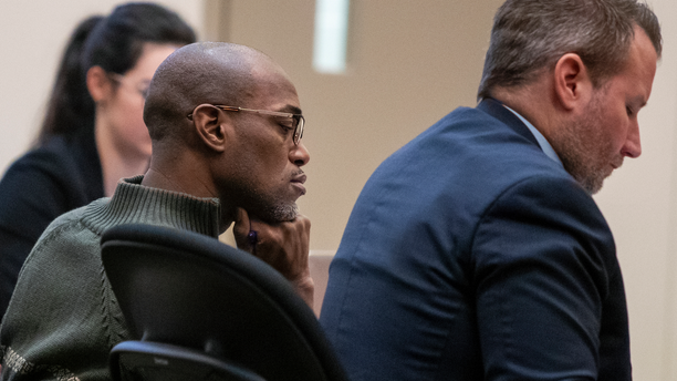 Quinn James, left, listens during Assistant Kent County Prosecutor Kellee Koncki's closing argument during his murder trial at the Kent County Courthouse in Grand Rapids on Wednesday, Feb. 27, 2019. James, accused of killing East Kentwood High student Mujey Dumbuya, 16, after she accused him of rape, is on trial this week charged with first-degree murder. (Cory Morse/The Grand Rapids Press via AP)