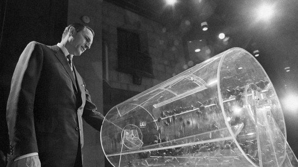 File-This Feb. 2, 1972, file photo shows Draft Director Curtis W. Tarr spinning one of the two Plexiglas drums in Washington as the fourth annual Selective Service lottery begins. The chairman of a panel considering changes to the U.S. military draft said Monday, Feb. 25, 2019, its recommendations to Congress won't be influenced by a federal judge's recent ruling that the current system is unconstitutional because it only applies to men. The military has not drafted anyone into service in more than 40 years, but American men must still register when they turn 18. Recent efforts to make registration also mandatory for women have set off intense debate in Washington.  (AP Photo/Charles W. Harrity, File)