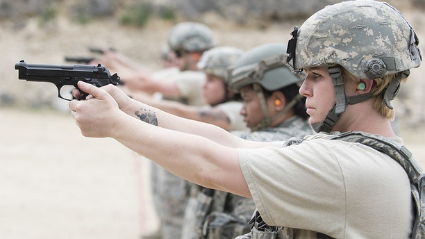 Senior Airman Clare Slater aiming M9 gun, in line with her colleagues, Gowen Field, Boise, Idaho. (Photo by Smith Collection/Gado/Getty Images)
