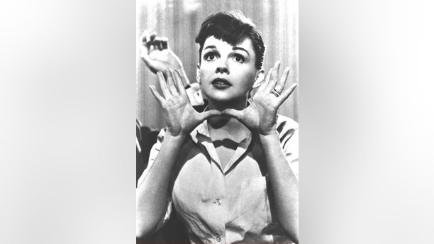 """Portrait of American popular singer and actress Judy Garland (1922 - 1969) as she makes the gesture later called """"Jazz Hands,"""" in a still from the film """"A Star is Born,"""" directed by George Cukor, circa 1954."""