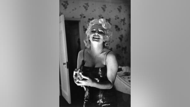 """Actress Marilyn Monroe gets ready to go see the play """"Cat On A Hot Tin Roof"""" playfully applying her makeup and Chanel No. 5 Perfume on March 24, 1955, at the Ambassador Hotel in New York City, New York."""