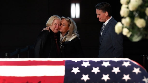 Rep. Debbie Dingell, D-Mich., center, consoled former Rep. Candice Miller, R-Mich., as Macomb County executive Mark Hackel, right, looked on at the casket of former Rep. John Dingell, lying in repose in Dearborn on Monday. (AP Photo/Paul Sancya)