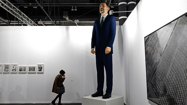 "A woman talks on her mobile phone next to ""Ninot"", a giant sculpture depicting Spain's King Felipe VI by artists Santiago Sierra and Eugenio Merino, during preparations for the International Contemporary Art Fair (ARCO) in Madrid on February 26, 2019 on the eve of its inauguration."