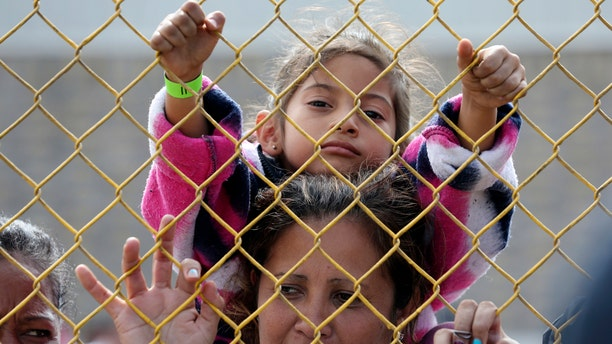 Six-year-old Daniela Fernanda Portillo Burgos sits on the shoulders of her mother, Iris Jamilet, 39, as they look out through the fence of a immigrant shelter in Piedras Negras, Mexico, Tuesday, Feb. 5, 2019.