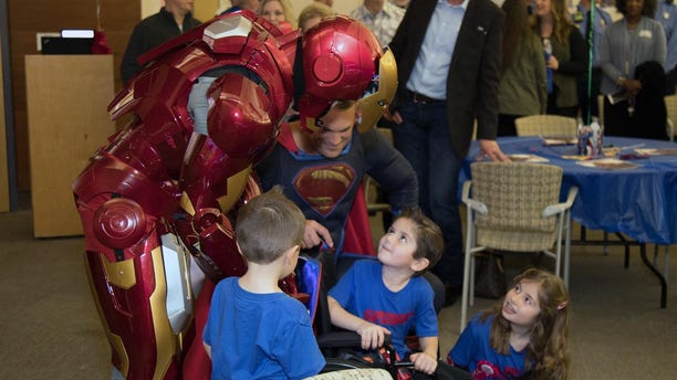 Owen Coulter, 5, celebrates his recovery with superheroes, Ironman and Superman, from the Austin Police Department.