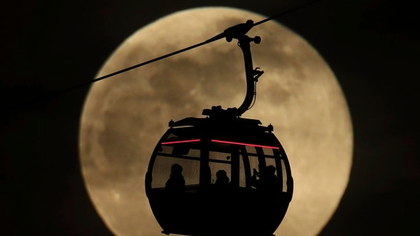 An Emirates Air Line cable cars is silhouetted against the backdrop of the 'supermoon' in Greenwich, London, Tuesday, Feb. 19, 2019.