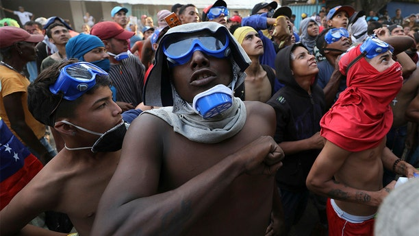 Venezuelan migrants under the Simon Bolivar International Bridge plead for people to support them with food and water so they can continue protesting in La Parada near Cucuta, Colombia, Sunday, on the border with Venezuela. (AP Photo/Fernando Vergara)