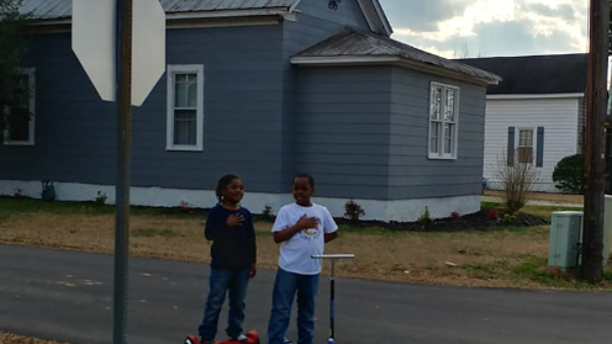 Two boys reciting the pledge of allegiance in front of a North Carolina fire station.
