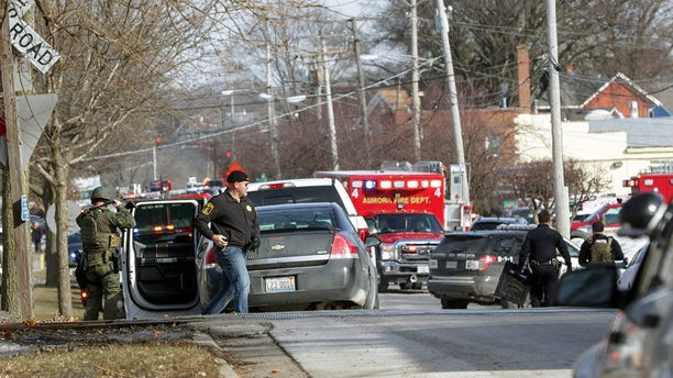 Law enforcement personnel gather near the scene of a shooting at an industrial park in Aurora, Ill., on Friday.