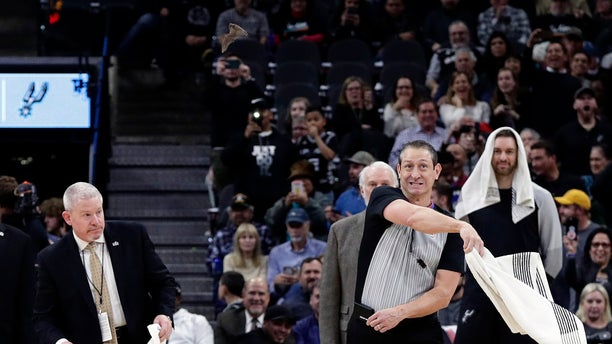 An official uses a towel to swat at a bat during the first half of an NBA basketball game between the San Antonio Spurs and the Brooklyn Nets, in San Antonio, Thursday, Jan. 31, 2019. (AP Photo/Eric Gay)