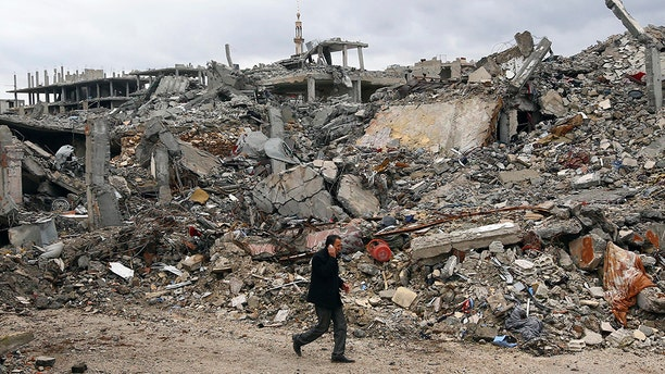 A man walks past damaged buildings in the northern Syrian town of Kobani January 30, 2015.