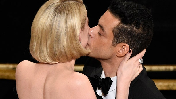 """Lucy Boynton, left, kisses Rami Malek in the audience after he is announced winner of the award for best performance by an actor in a leading role for """"Bohemian Rhapsody"""" at the Oscars on Sunday, Feb. 24, 2019, at the Dolby Theatre in Los Angeles. (Photo by Chris Pizzello/Invision/AP)"""
