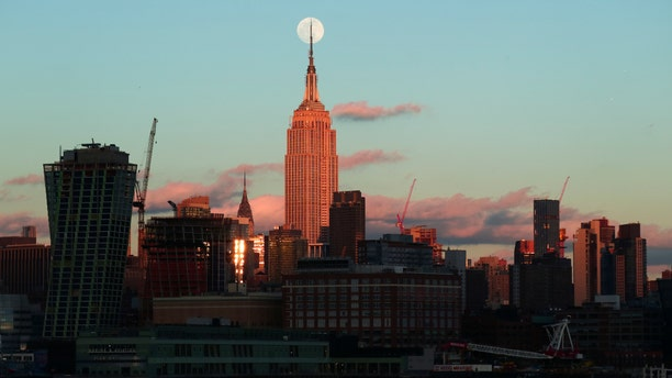 The almost full super snow moon rises at sunset behind the Empire State Building and Chrysler Building in New York City on Feb. 18, 2018 photographed from Hoboken, New Jersey. (Gary Hershorn/FOX News)