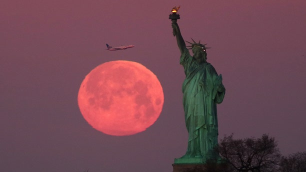 The 'super snow moon' sets behind the Statue of Liberty in New York City as the sun rises on Feb. 19, 2019.