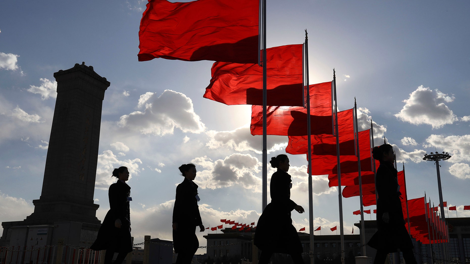 Bus ushers walk past red flags on Tiananmen Square during a plenary session of the Chinese People's Political Consultative Conference (CPPCC) at the Great Hall of the People in Beijing Monday, March 11, 2019 - file photo.