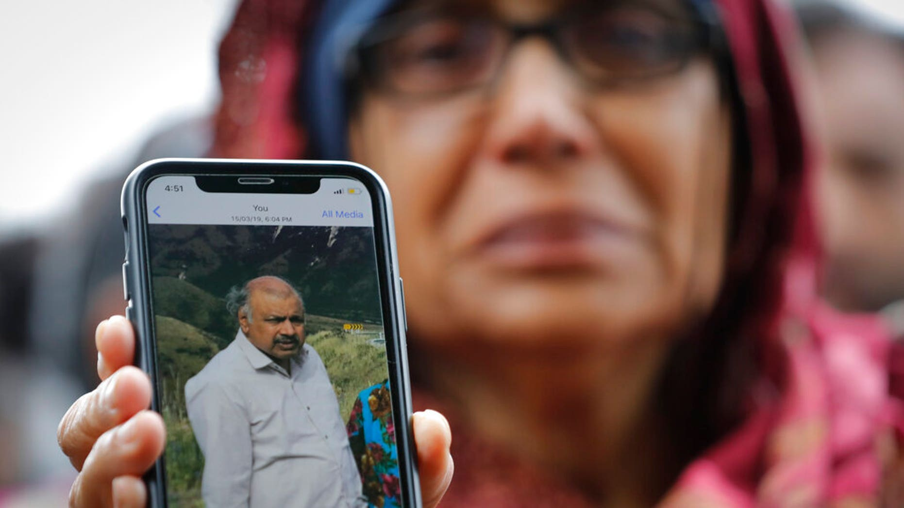 Akhtar Khokhur, 58, shows a picture of her missing husband Mehaboobbhai Khokhar during an interview outside an information center for families this weekend in Christchurch, New Zealand. (AP Photo/Vincent Thian)