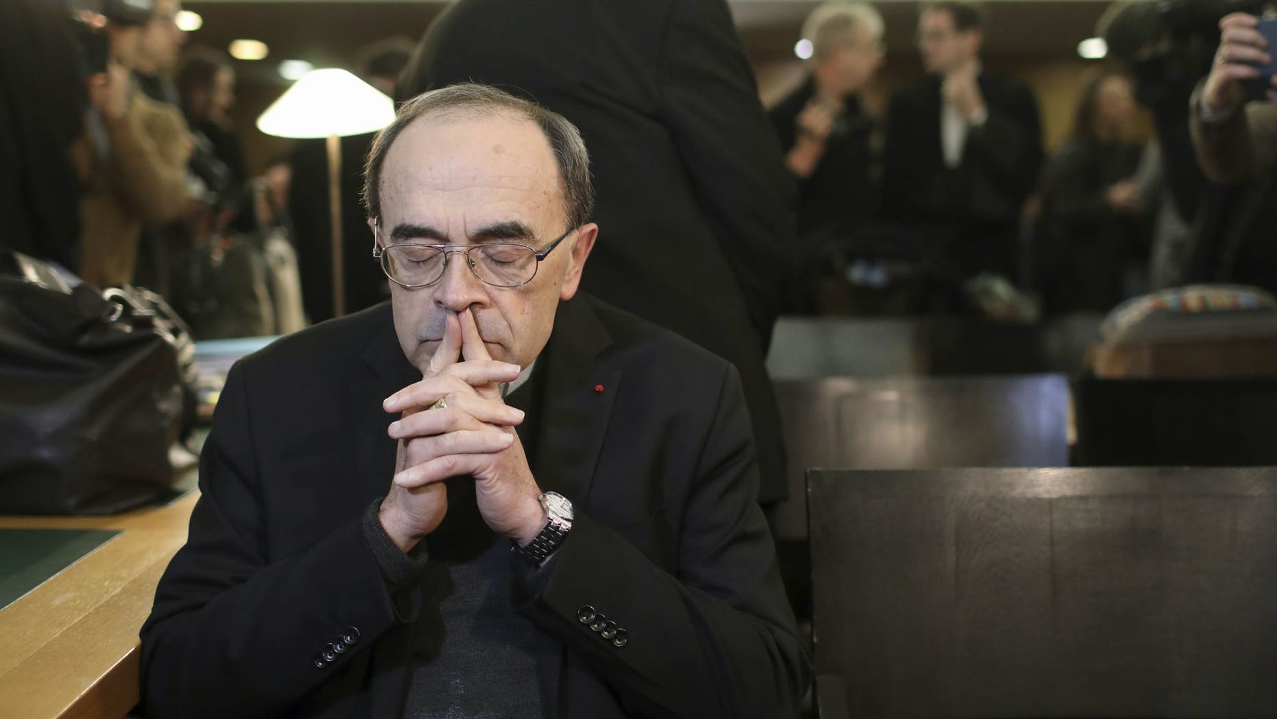 In this Jan. 7, 2019 file photo, French Cardinal Philippe Barbarin waits for the start of his trial at the Lyon courthouse, central France. A French court has found top Catholic official Cardinal Philippe Barbarin guilty for failing to report to justice accusations against a pedophile priest. In a surprise decision Thursday, March 7, 2019 in France's most important church sex abuse trial, the Lyon court handed Barbarin a six-month suspended prison sentence for not reporting the facts in the period between July 2014 and June 2015.