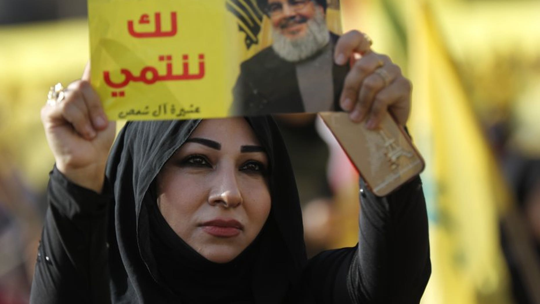 """In this April 13, 2018, file photo, a supporter of Hezbollah leader Sayyed Hassan Nasrallah holds up his portrait with Arabic words that read: """"We belong with you,"""" during an election campaign speech in a southern suburb of Beirut, Lebanon."""