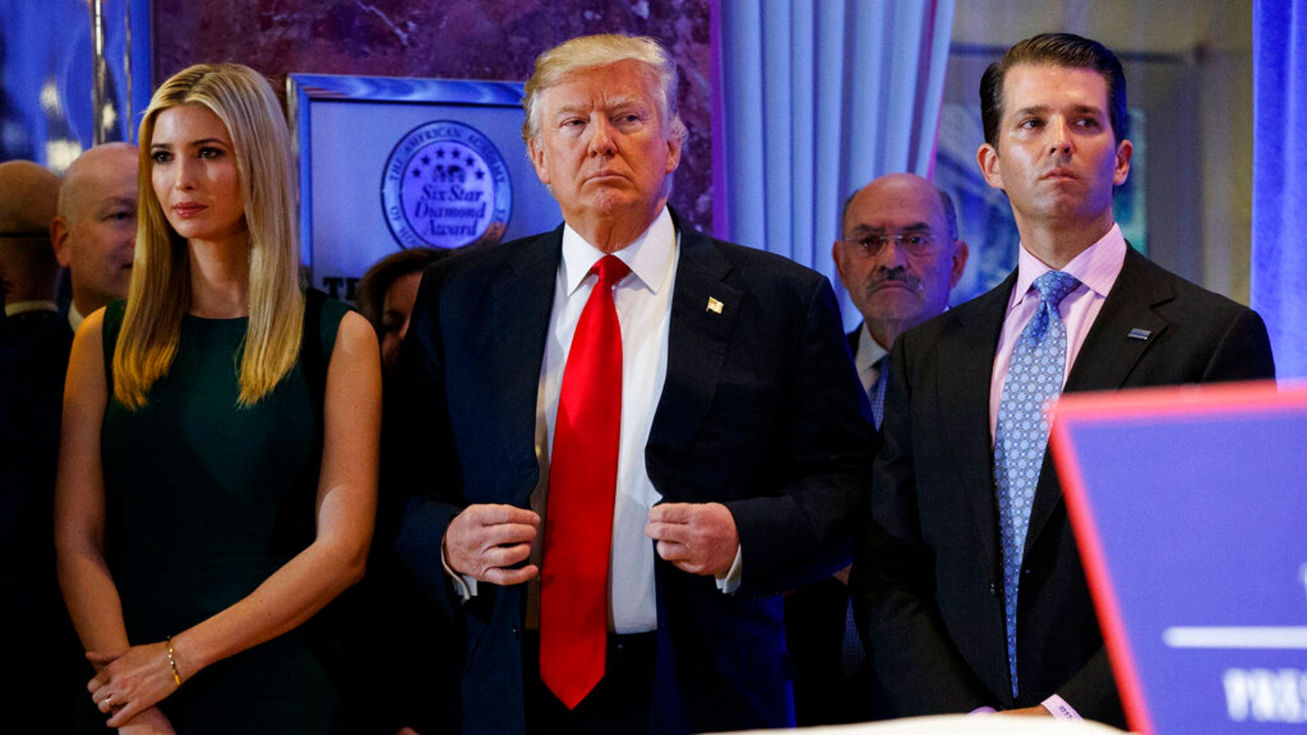 FILE: President-elect Donald Trump, center, stands next to Allen Weisselberg, second from left, Donald Trump Jr., right and Ivanka Trump, left, at a news conference in the lobby of Trump Tower in New York.
