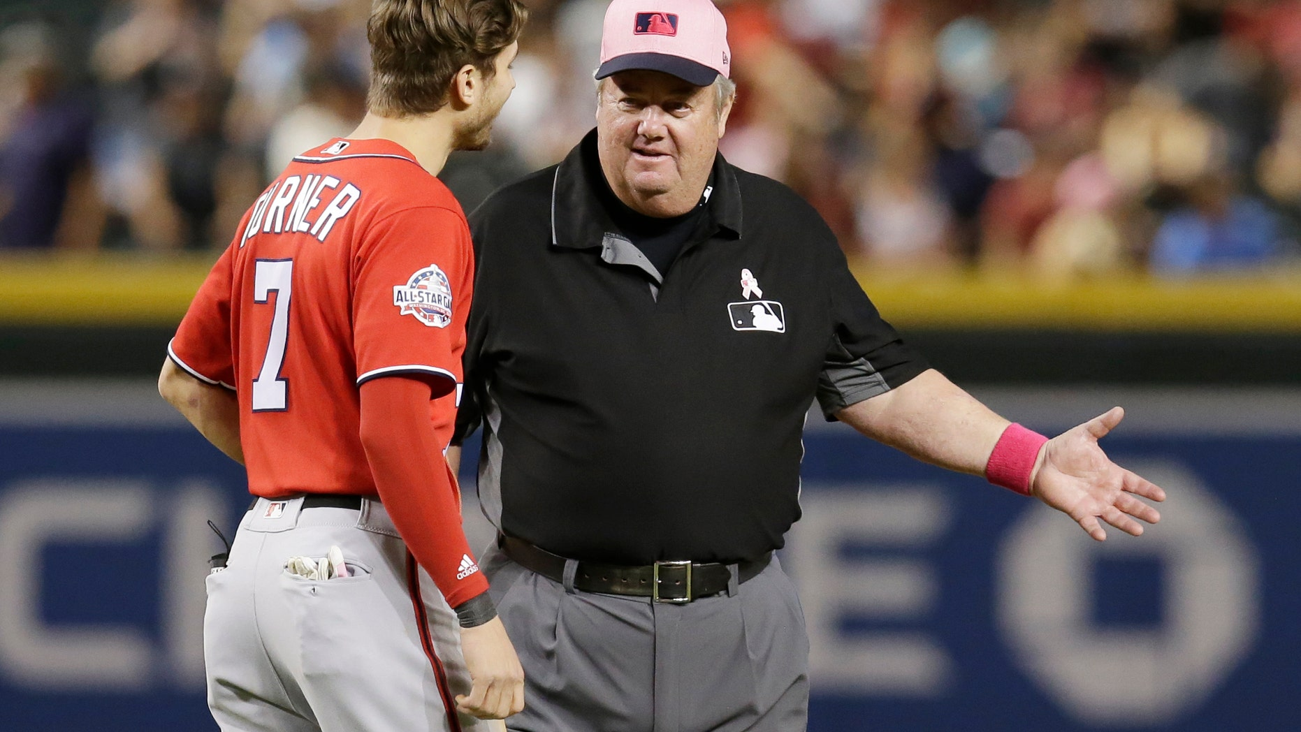 FILE - In this May 13, 2018, file photo, MLB umpire Joe West, right, talks with a player in the ninth inning during a baseball game between the Arizona Diamondbacks and the Washington Nationals in Phoenix. West, who has umpired more than 5,000 big league games, said the 2016 TrackMan computer system test was far from perfect.