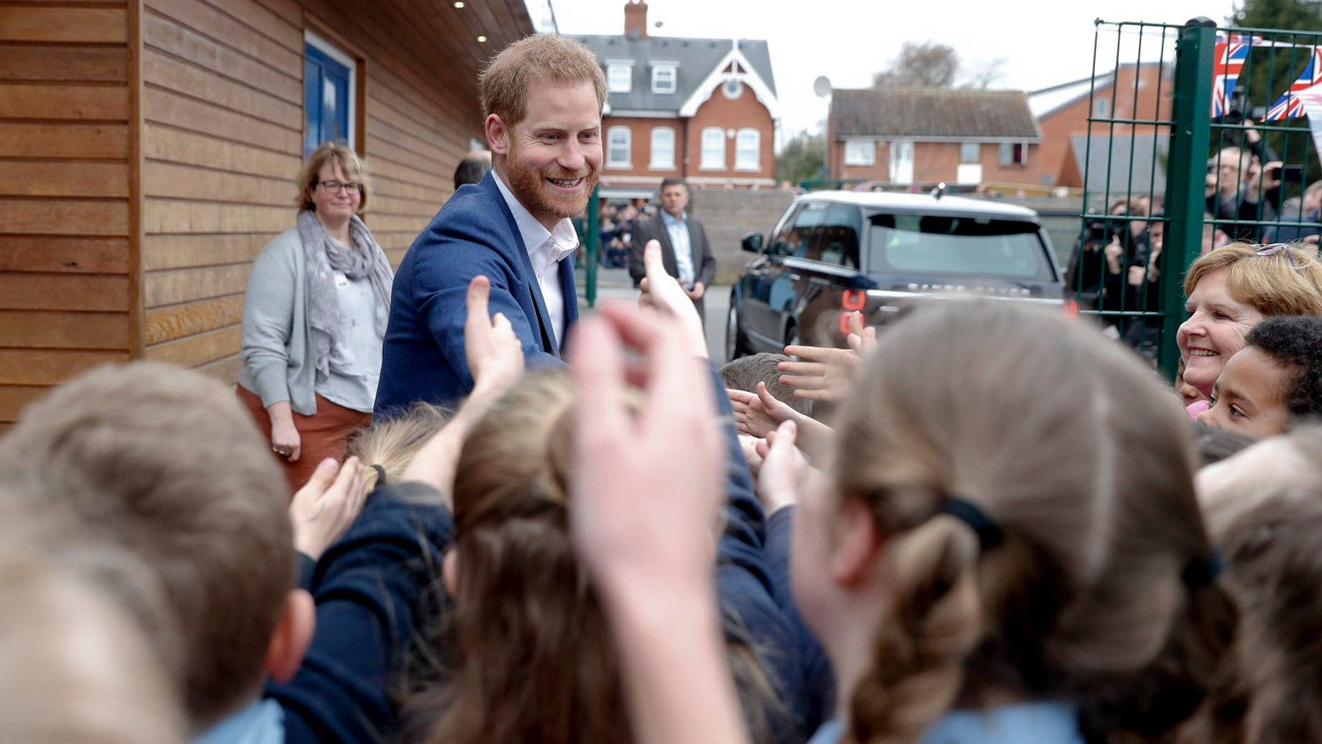 Britain's Prince Harry shakes hands with pupils from St. Vincent's Catholic Primary School.