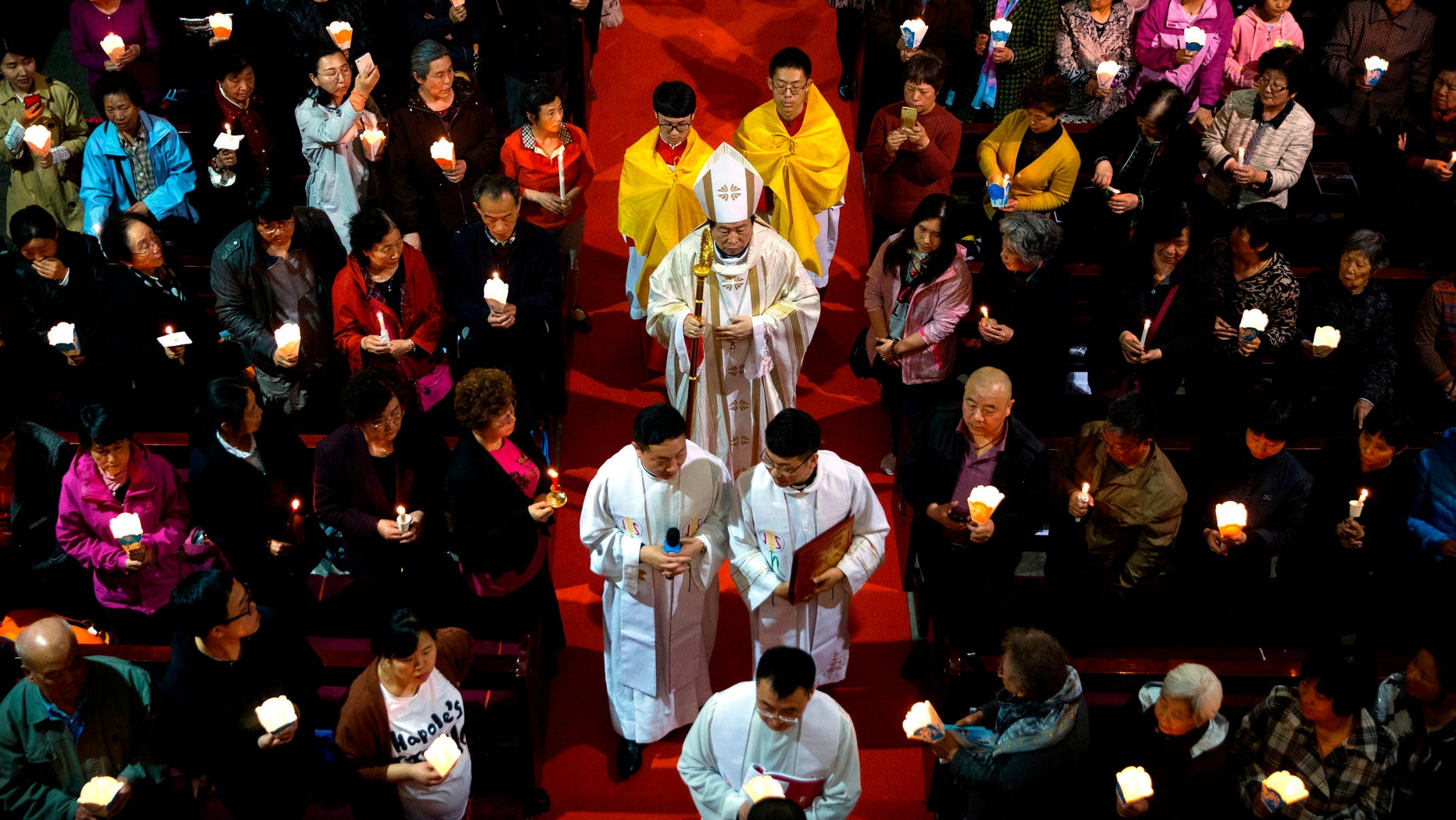 FILE - In this Saturday, March 31, 2018, file photo, Chinese Bishop Joseph Li Shan, center, walks down the aisle during a Holy Saturday Mass on the evening before Easter at the Cathedral of the Immaculate Conception, a government-sanctioned Catholic church in Beijing. (AP Photo/Mark Schiefelbein, File)