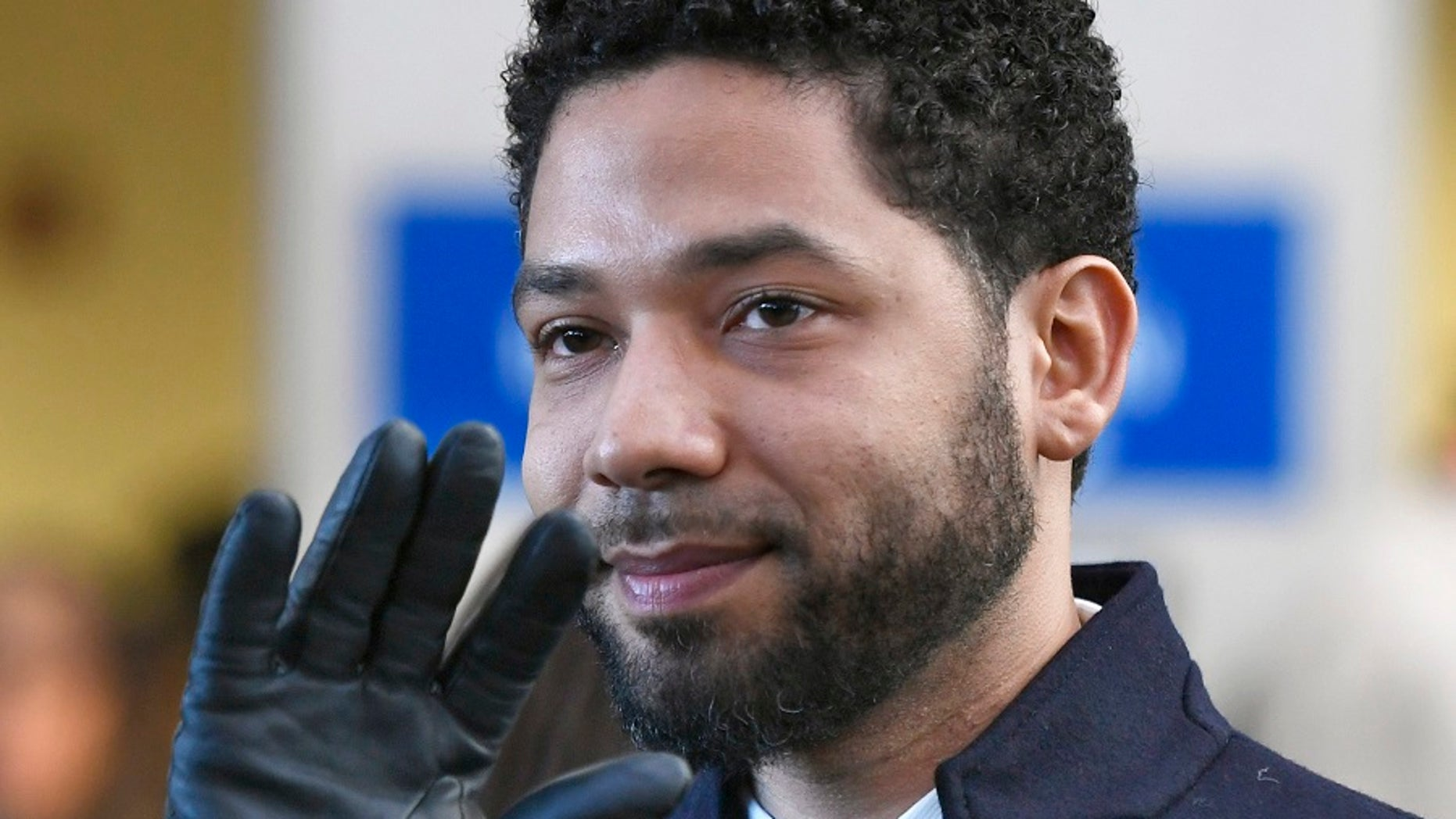 Actor Jussie Smollett smiles and waves to supporters before withdrawal Cook County (Ill.) Court after his charges were forsaken in Chicago. (Associated Press)