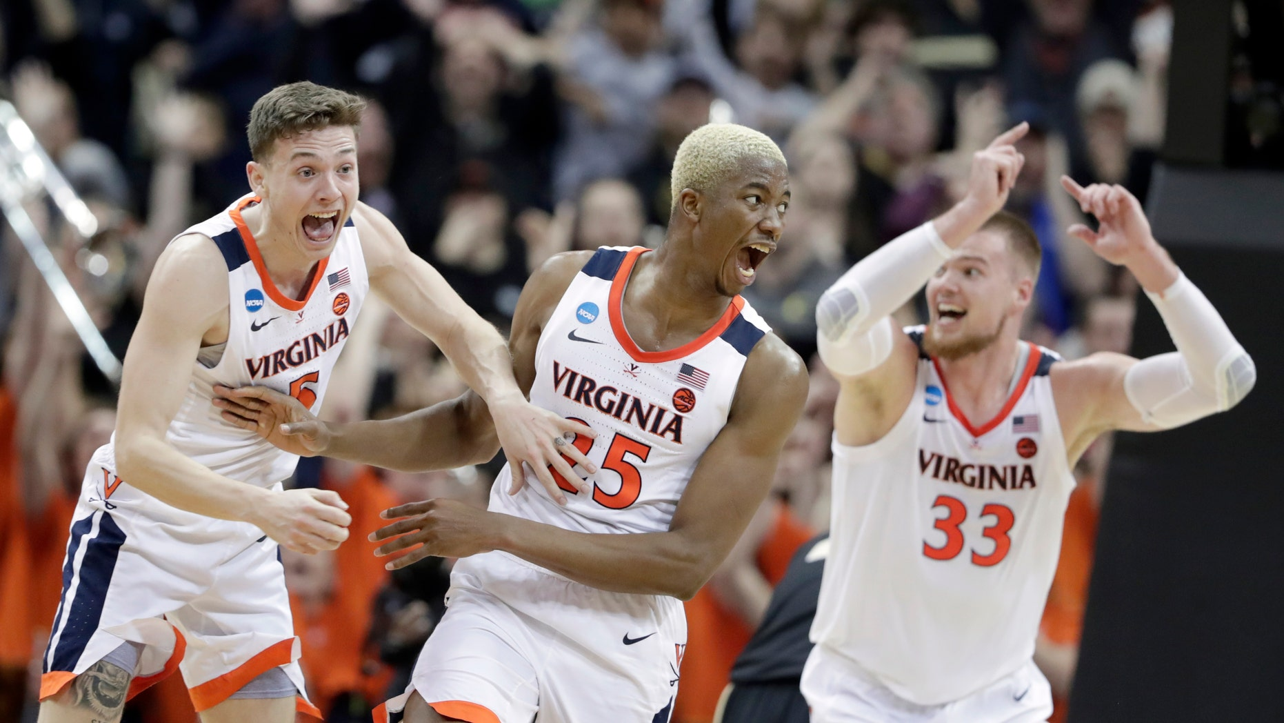 Virginia's Mamadi Diakite, center, reacts with teammates Kyle Guy and Jack Salt (33) after hitting a shot to send the game into overtime in the men's NCAA Tournament college basketball South Regional final game against Purdue, Saturday, March 30, 2019, in Louisville, Ky. (Associated Press)