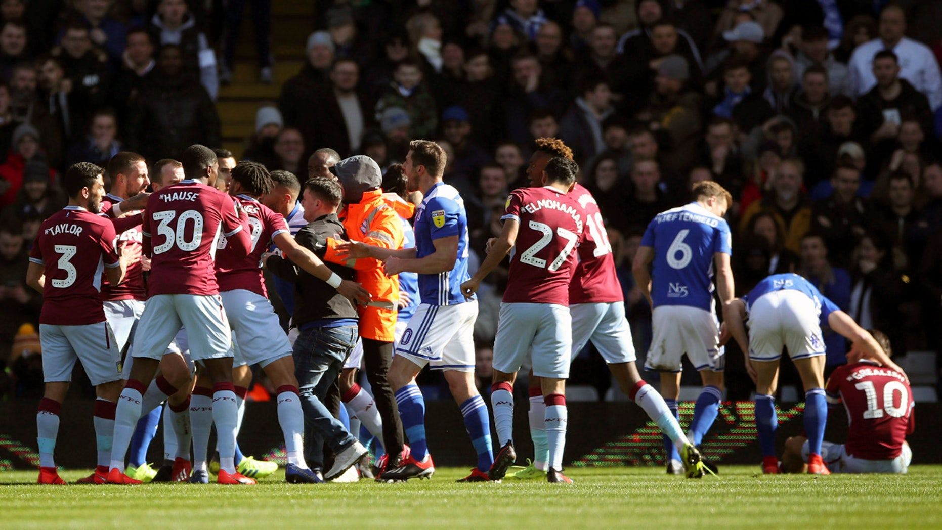 A fan was removed after attacking Aston Villa's Jack Grealish, right, on the pitch during the Sky Bet Championship soccer match at St Andrew's Trillion Trophy Stadium, Birmingham, England, on Sunday. (Nick Potts/PA via AP)