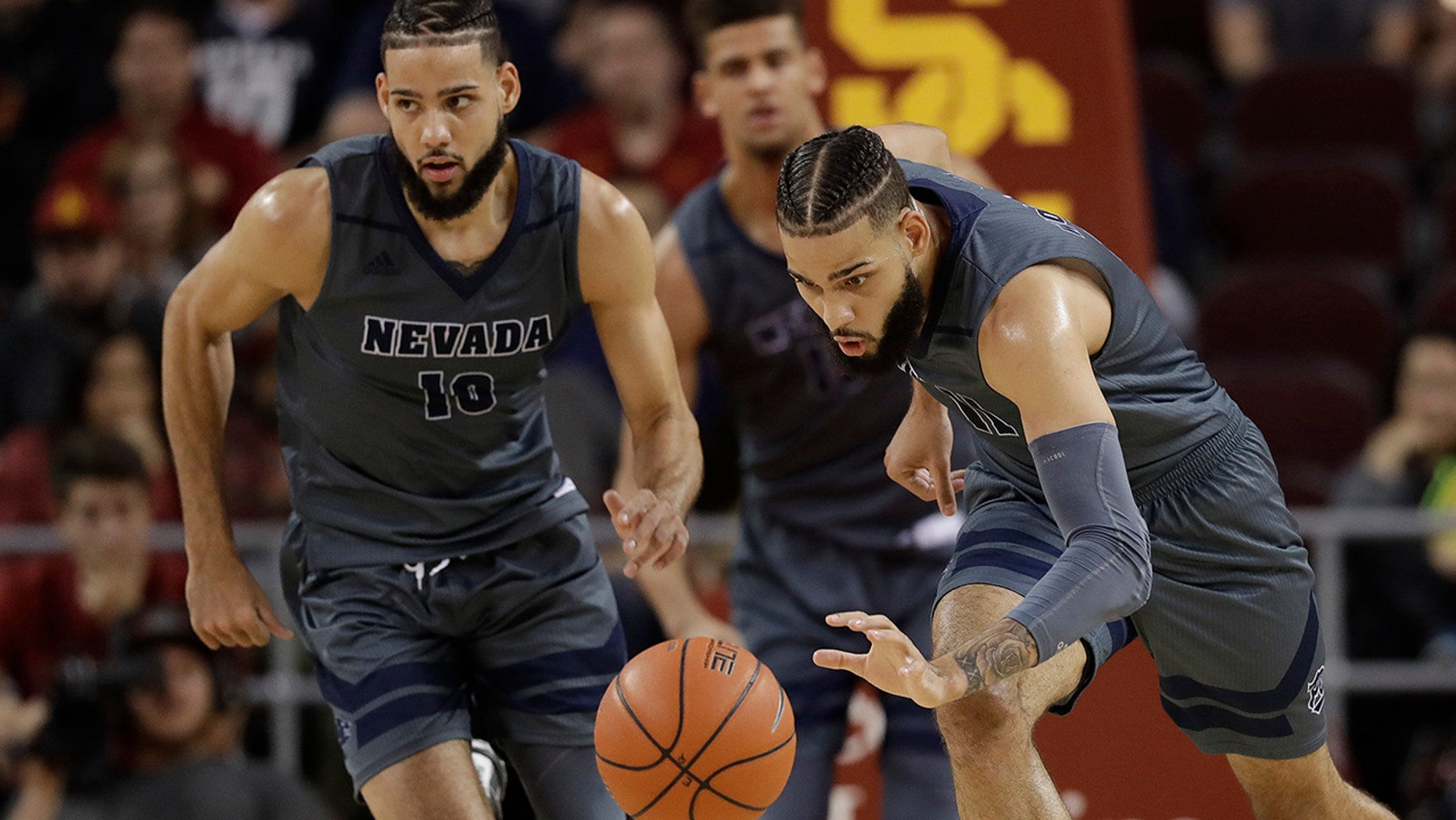 FILE - In this Dec. 1, 2018, file photo, Nevada forward Cody Martin, right, dribbles downcourt as his twin brother Caleb Martin, left, trails during the second half of an NCAA college basketball game against Southern California in Los Angeles.