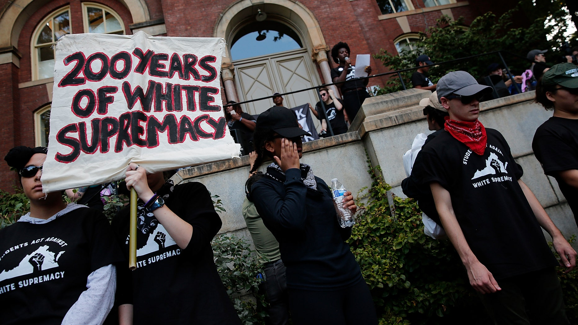 """File photo - Protesting with the Students Act Against White Supremacy group speaks at the University of Virginia's campus during an event marking a one-year anniversary of a deadly clash of white supremacists and counter-protocols on August 1<div class=""""e3lan e3lan-in-post1""""><script async src=""""//pagead2.googlesyndication.com/pagead/js/adsbygoogle.js""""></script> <!-- Text_Image --> <ins class=""""adsbygoogle""""      style=""""display:block""""      data-ad-client=""""ca-pub-6192903739091894""""      data-ad-slot=""""3136787391""""      data-ad-format=""""auto""""      data-full-width-responsive=""""true""""></ins> <script> (adsbygoogle = window.adsbygoogle 