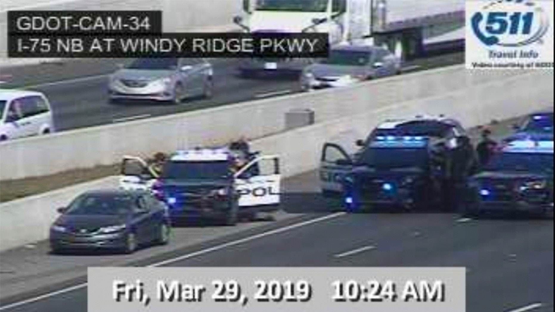 """In this image made from video provided by the Georgia Department of Transportation, Marietta Police block southbound lanes on Interstate-75, near Marietta, Ga., North of Atlanta, Friday, March 29, 2019. Marietta police said in a brief statement that the southbound lanes of Interstate 75 were shut down Friday morning due to a motorist stopped on the freeway just northwest of Atlanta. Police described the motorist as a """"non-compliant driver."""" (Georgia Department of Transportation via AP)"""