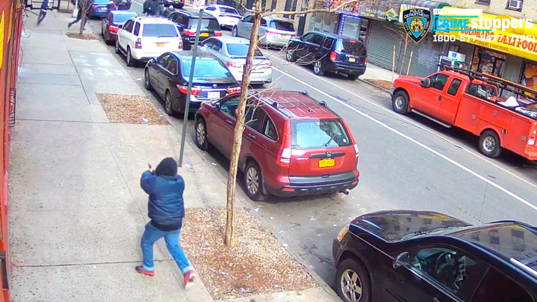 In this Feb. 22, 2019 image taken from surveillance video released by the New York City Police Department, a gunman identified by the NYPD as 16-year-old Edgar Garcia opens fire on a crowded street in the Bronx borough of New York. No one was hit by the gunfire. (New York City Police Department via AP)