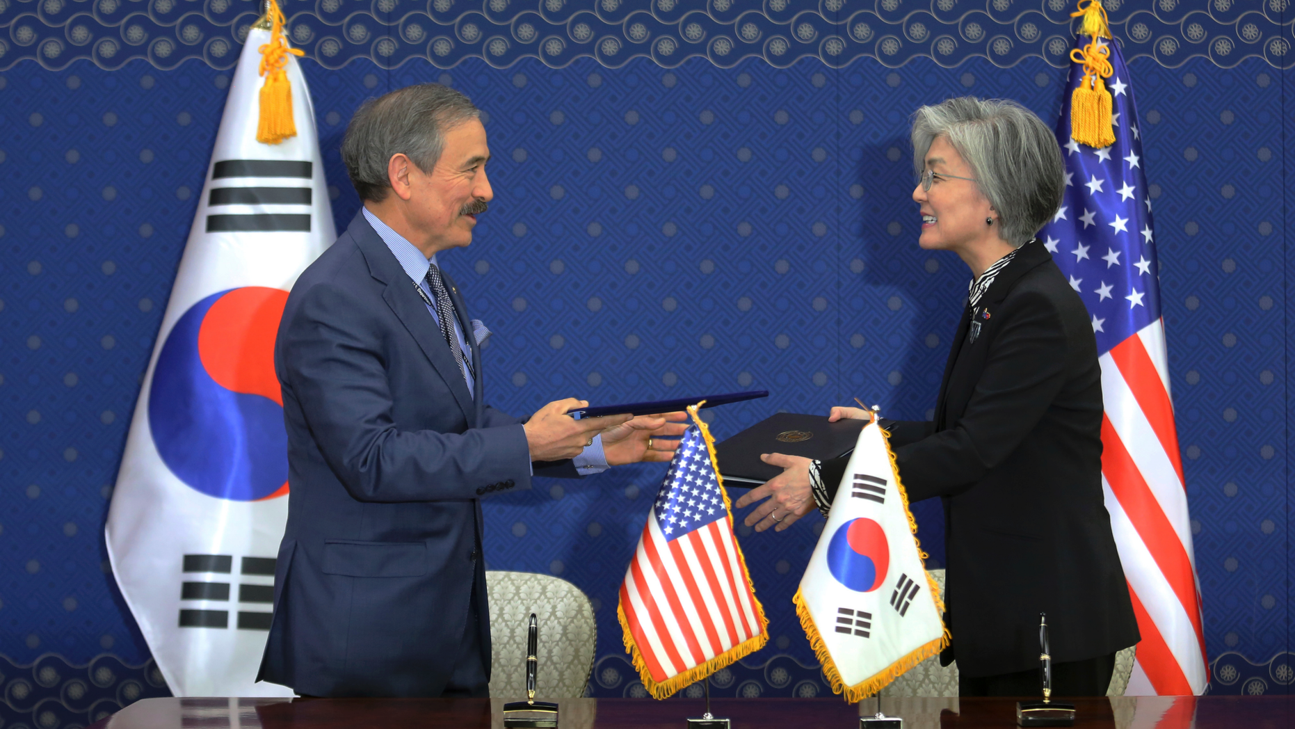South Korean Foreign Minister Kang Kyung-wha, right, and U.S. Ambassador to South Korea Harry Harris exchange documents at Foreign Ministry in Seoul, South Korea, Friday, March 8, 2019. South Korea and the United States have formally signed a deal that increases Seoul's financial contribution for the deployment of U.S. troops in the Asian country. (AP Photo/Ahn Young-joon, Pool)