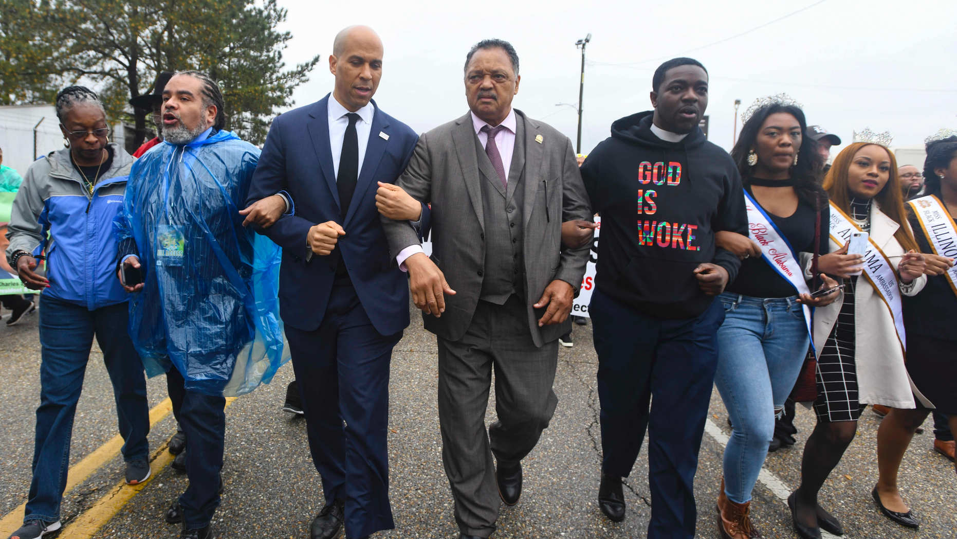 """U.S. Sen. Cory Booker, D-N.J., third from left, and the Rev. Jesse Jackson march to cross the Edmund Pettus Bridge Sunday, March 3, 2019, during the Bloody Sunday commemoration in Selma, Ala.  The infamous """"Bloody Sunday"""" on March 7, 1965, galvanized support for the passage of the Voting Rights Act that year. (AP Photo/Julie Bennett)"""
