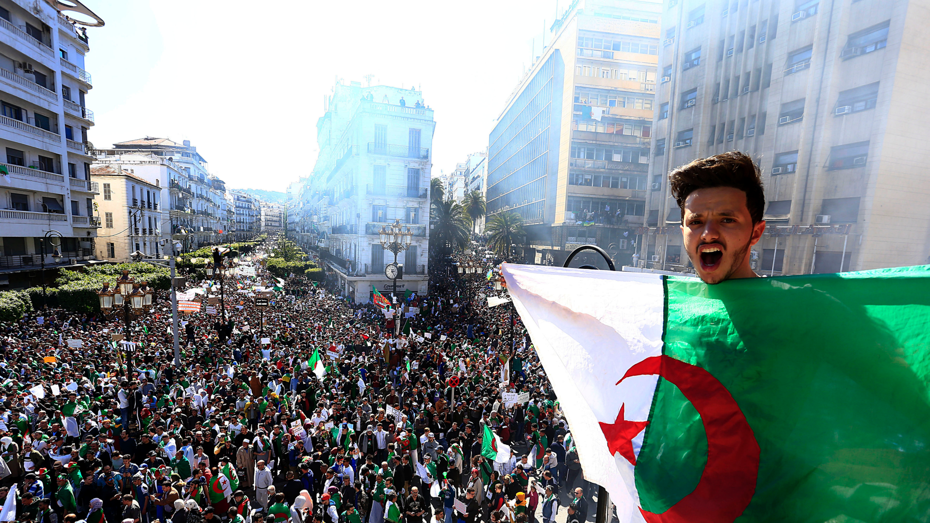 Algerian shouts as he holds the national flag during a protest in Algiers, Algeria, Friday, March 15, 2019. Tens of thousands of people gathered Friday in Algeria's capital and other cities amid heavy security for what could be decisive protests against longtime leader Abdelaziz Bouteflika. (AP Photo/Toufik Doudou)