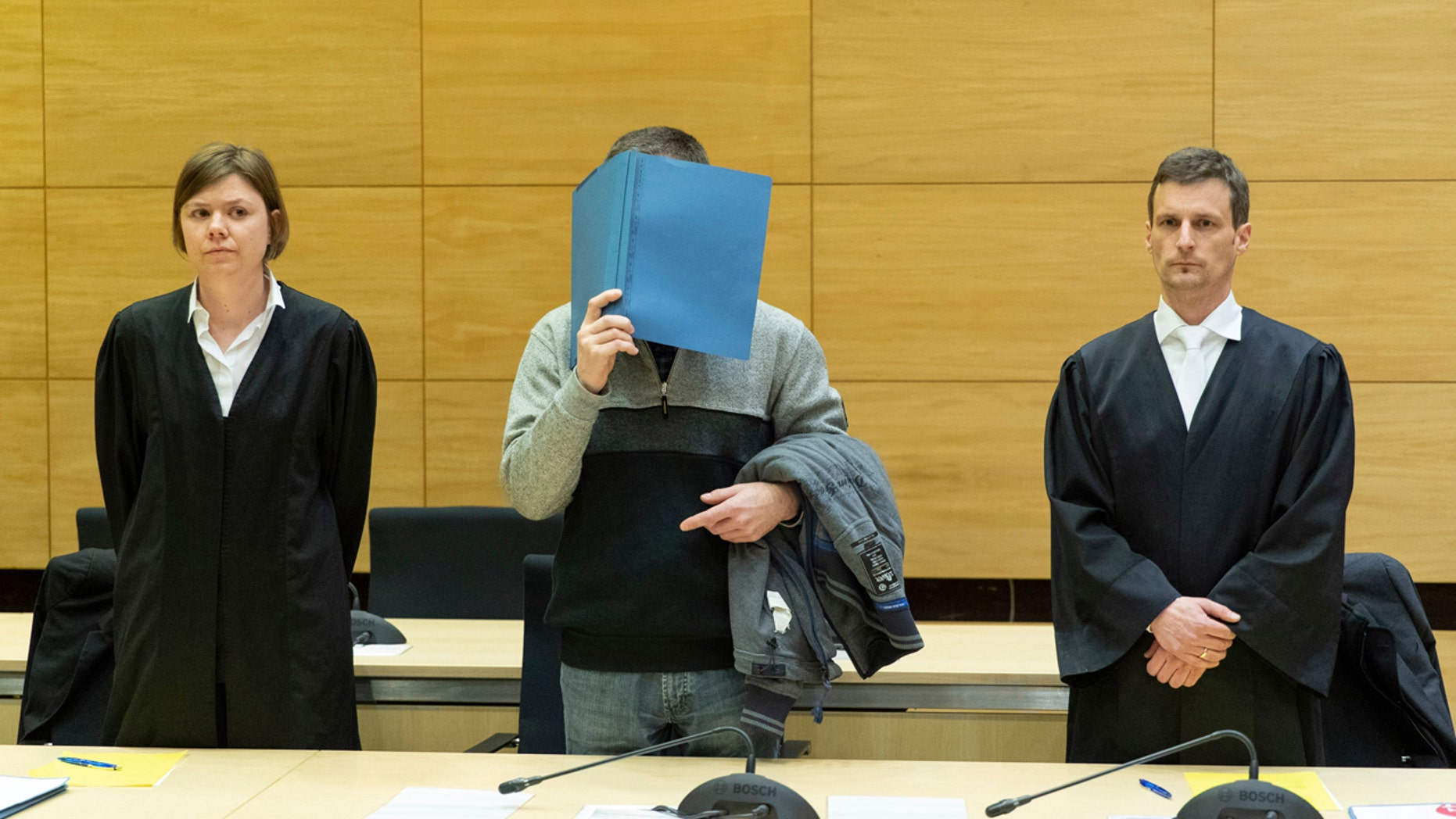 A 57-year old defendant hides his face at the courtroom in Bielefeld, Germany, Thursday, March 7, 2019.