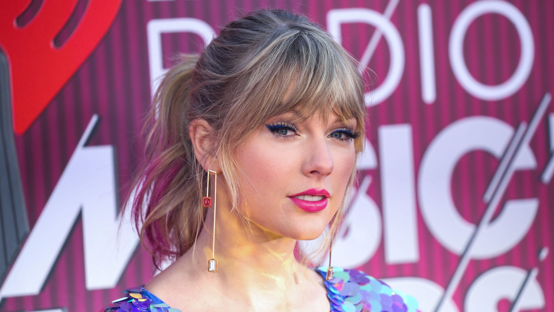 Singer Taylor Swift wearing a Rosa Bloom romper, Sophia Webster shoes, State Property Fine Jewellery earrings, rings by Fernando Jorge, Stefere, Jacquie Aiche, and EF Collection, and an Edie Parker bag arrives at the 2019 iHeartRadio Music Awards held at Microsoft Theater at L.A. Live on March 14, 2019 in Los Angeles, California, United States.