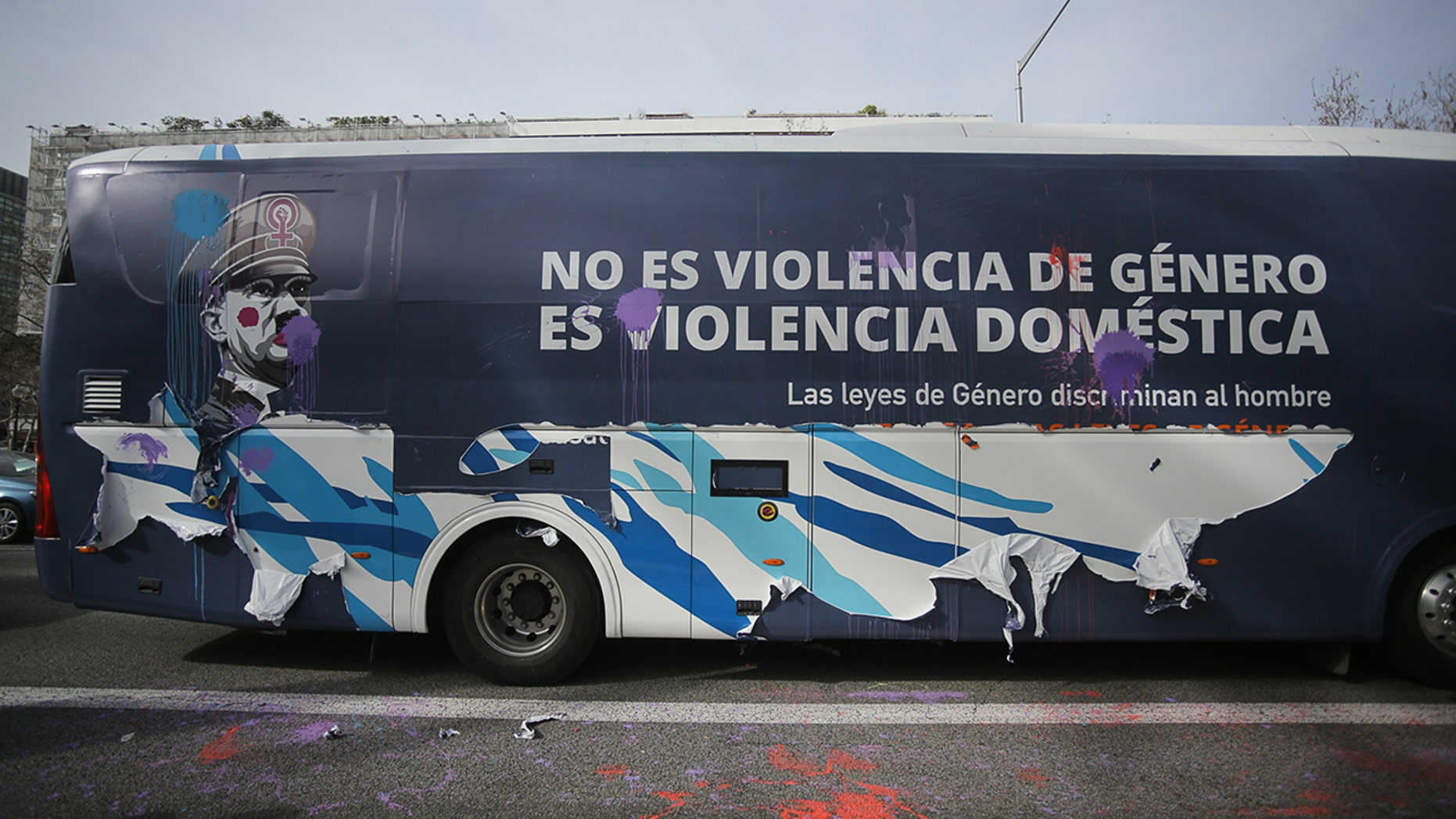 """A bus chartered by conservative association """"Hazte Oir"""" (Make yourself heard) displaying an image of the leader of the Nazi Party, Adolf Hitler with make-up on his face and sporting a feminist symbol on his hat, next to a legend reading """"It is not gender violence, it is domestic violence"""" in Barcelona on March 4, 2019, after protesters threw paint to it and peeled off part of its vinyl decoration."""
