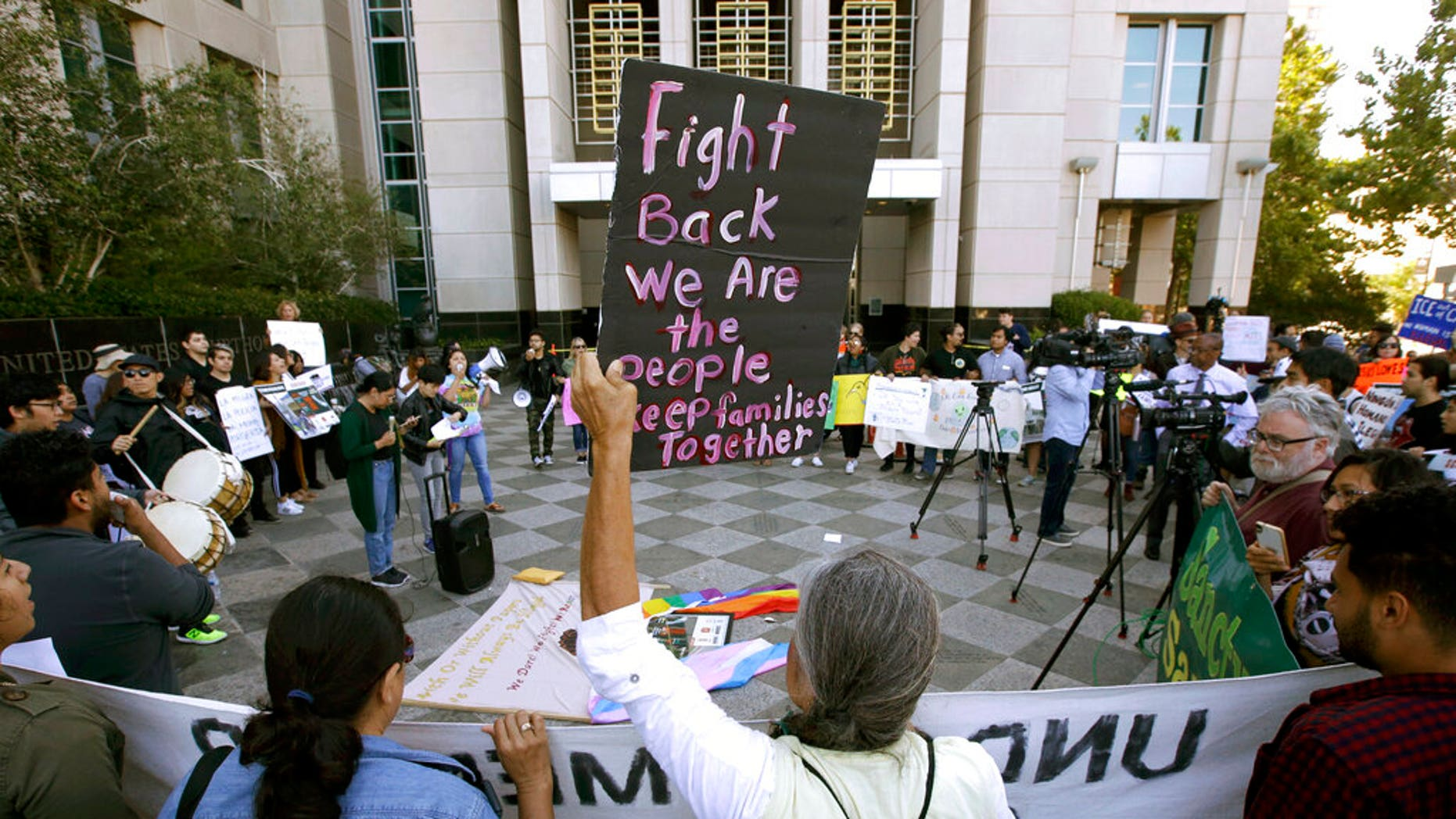 "FILE - In this June 20, 2018, file photo, protesters demonstrate outside the federal courthouse in Sacramento, Calif., where a judge heard arguments over the U.S. Justice Department's request to block three California laws that extend protections to people in the country illegally. The Justice Department told The Associated Press at the end of February 2019 that 28 jurisdictions, including Sacramento, that were targeted in 2017 over what it considered ""sanctuary"" policies have been cleared for law enforcement grant funding. (AP Photo/Rich Pedroncelli, File)"