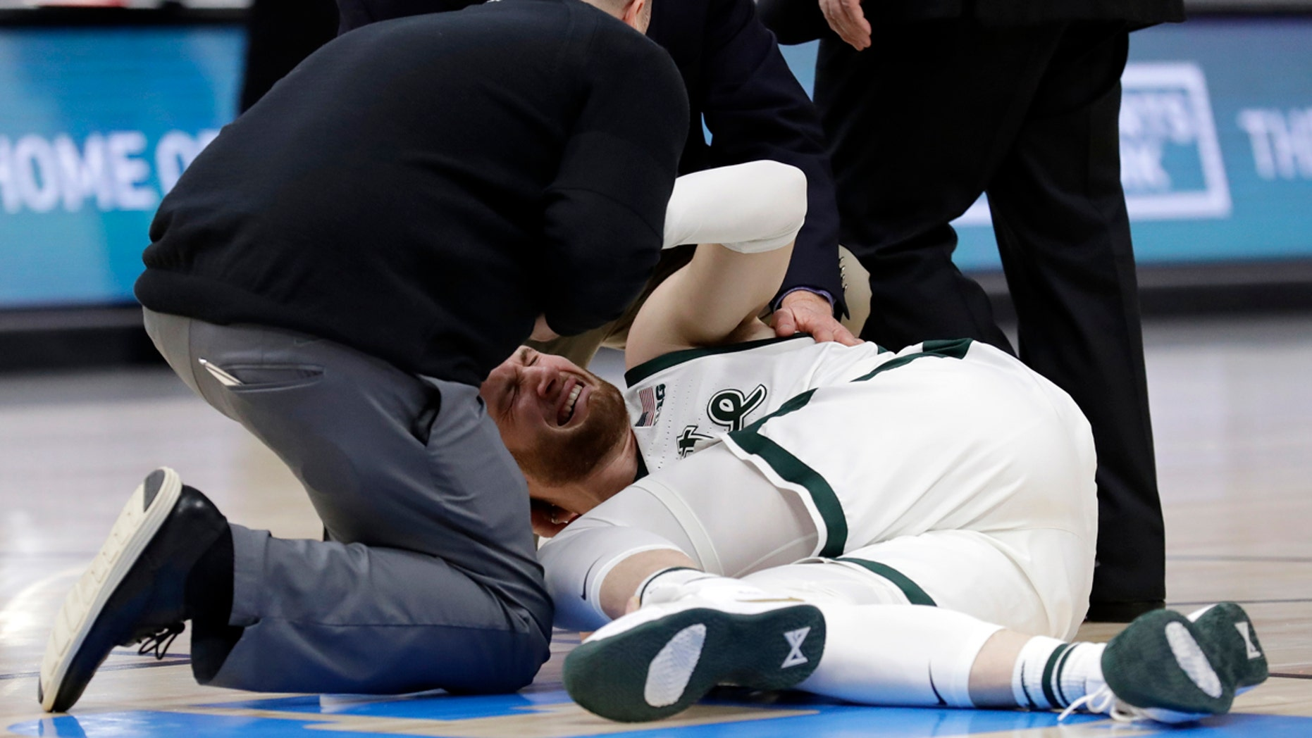 March 17: Medical personnel checks on Michigan State's Kyle Ahrens during the first half of an NCAA college basketball championship game against Michigan in the Big Ten Conference tournament.